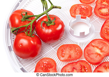 Fresh tomato on food dehydrator tray - Fresh tomato with...