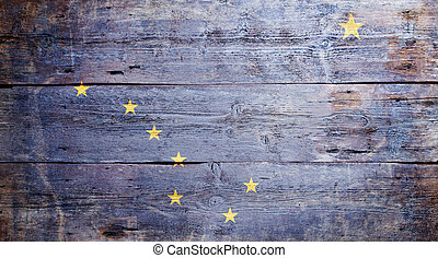 Flag of Alaska painted on grungy wood plank background