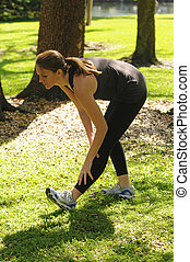 young woman stretching outdoors after run