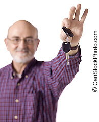 old man holding a car key - Blurred image of an old man...