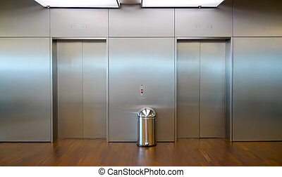 Two elevator doors - Two brushed metal elevator doors in a...