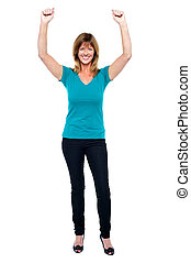 Excited woman in celebration mood with raised arms - Joyous...
