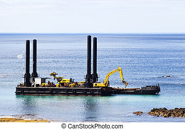 Dredger near the shore cleaning the bay