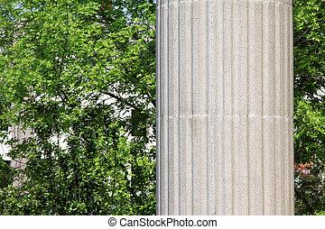 gray stone pillar and green trees in a garden