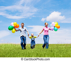happy family with balloons running outdoor on a warm summer...