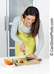 Woman cutting cucumber and vegetables