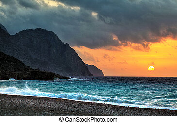 Sougia sunset - The sun dips below threatening clouds at...