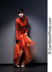 Trendy Brunette posing in Red Dress. Studio Shot
