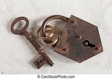 Wedlock - Wedding rings boud by a rusty old padlock