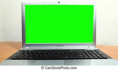 Notebook with a green screen - Close-up of a laptop with a...