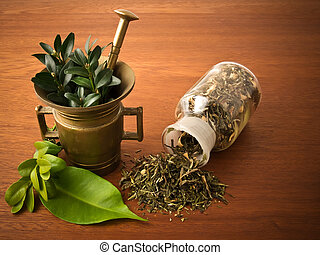 Mortar and pharmacy bottle, with herbs. On the wood table.