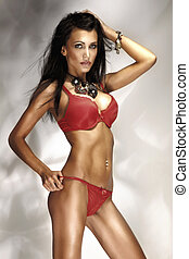 Photo of sexy brunette woman posing in red lingerie and amazing jewellery. Long dark hair.