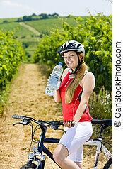 biker with bottle of water in vineyard, Czech Republic