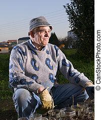 Farmer sitting and looking sideways in a flash strobist shot