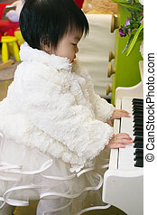 A baby playing on a toy piano