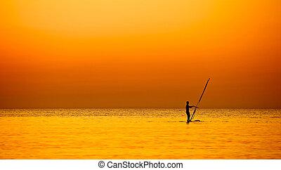 Evening windsurfing - man on Windsurf riding on sunset ocean
