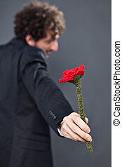Man giving fabric rose - Boy with glasses and jacket is...