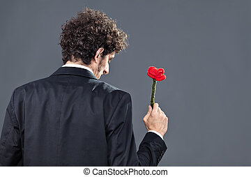Man giving fabric rose - Boy is donating a fabric red rose...