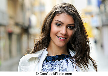 Beautiful woman smiling in urban background - Portrait of a...
