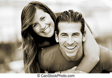 Smiling young man piggybacking his pretty girlfriend -...
