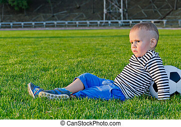 Little boy relaxing with his soccer ball lying back on a...