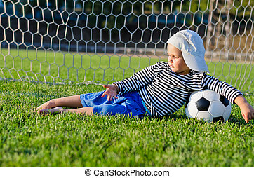 Small boy lying in the goalposts - Small barefoot boy in a...