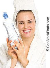 Smiling young woman in bathrobe with water bottle