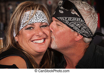 Mature Bearded Man Kisses Woman - Smiling woman in bandanna...