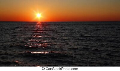 Great Lakes Sunset - The setting sun, low on the horizon,...