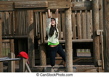 Teenage girl playing at playground on monkey bars