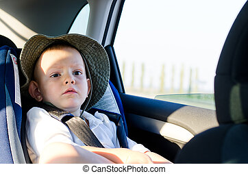Cute little boy passenger in a car sitting quietly on the...