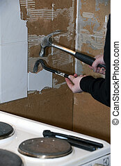 Renovation kitchen - Tile being removed, young woman doing...