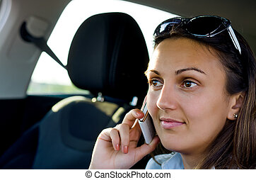Woman using her mobile in a car