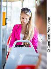 Pretty, young woman on a streetcar/tramway, during her...