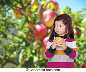 Beautiful girl eating an apple with a fruit-tree