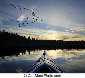 Kayak and Geese at Sunset - Kayak on the lake at sunset with...