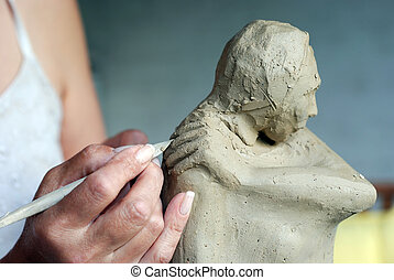 Clay - Close up to sculptors hand and her sculpture while...