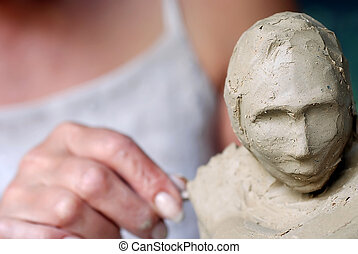Clay - Close up to a sculptors hand and female sculpture...