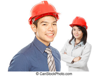 Man and Woman Wearing Hardhats - A man and a woman wearing...