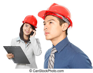 Young Professionals - A man and a woman wearing hardhats and...
