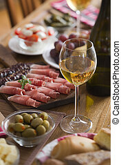 White wine - Glass of white wine on a table full with food