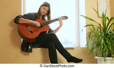 Teen Girl Playing Guitar - Teen girl learning to play guitar...
