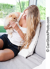 young woman playing with her tinny dog