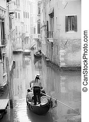 Venice cityscape - Gondolier guiding a gondola in narrow...
