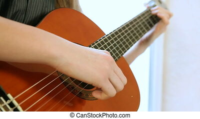 Teen Girl Playing Guitar Close-up