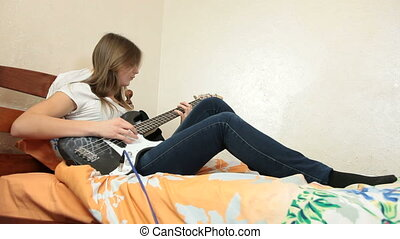 Teen Girl Playing Bass Guitar At Home