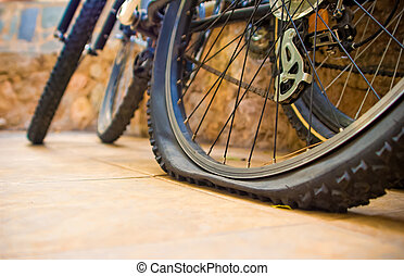 Bicycle flat tyre - Two bicycles at the yard, one with a...