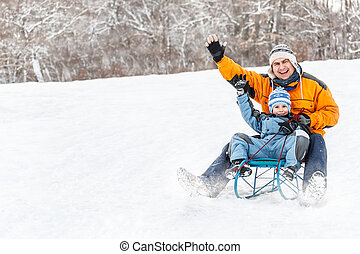 Winter time - Young father and son sledding at winter time
