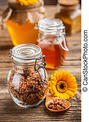 Propolis granule in glass jar decorated with yellow flower
