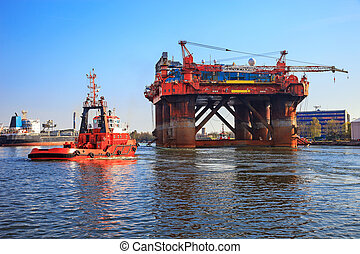 Oil Rig - Oil rig in the company of a tug boats enters a...